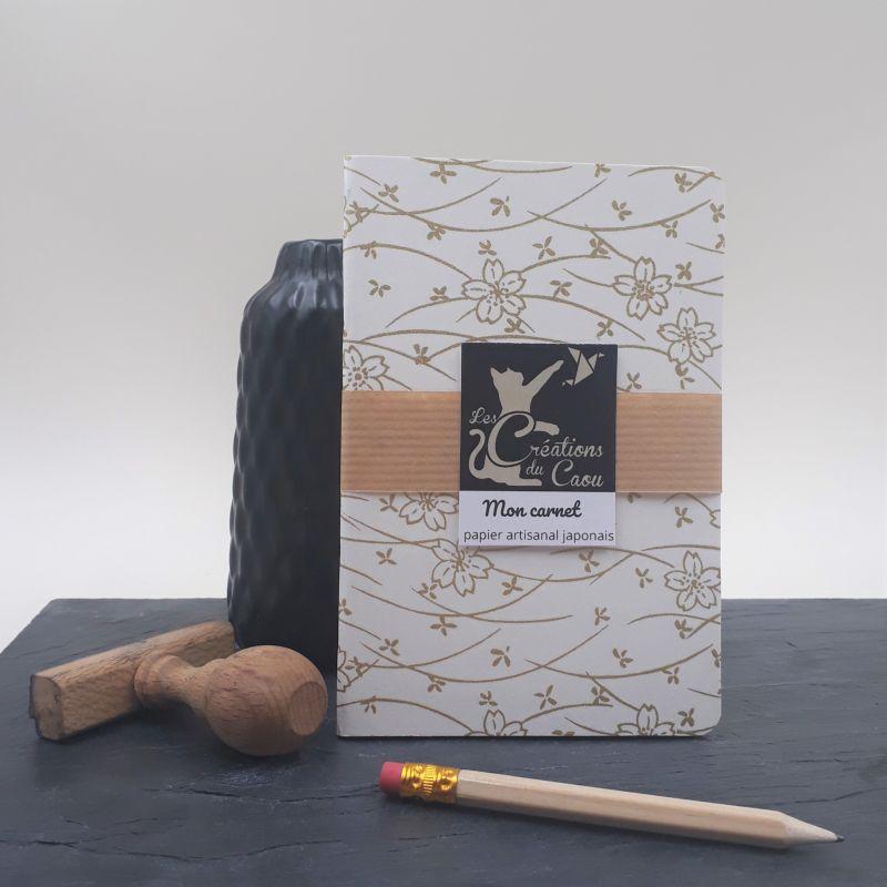Carnet de notes au format A6. La couverture est recouverte à la main d'un papier japonais écru au motif fleur doré.