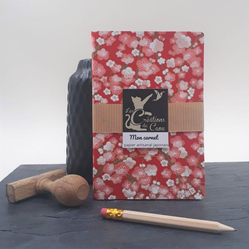 Carnet de notes au format A6. La couverture est recouverte à la main d'un papier japonais rouge au motif de fleurs de pruniers rose et blanches..