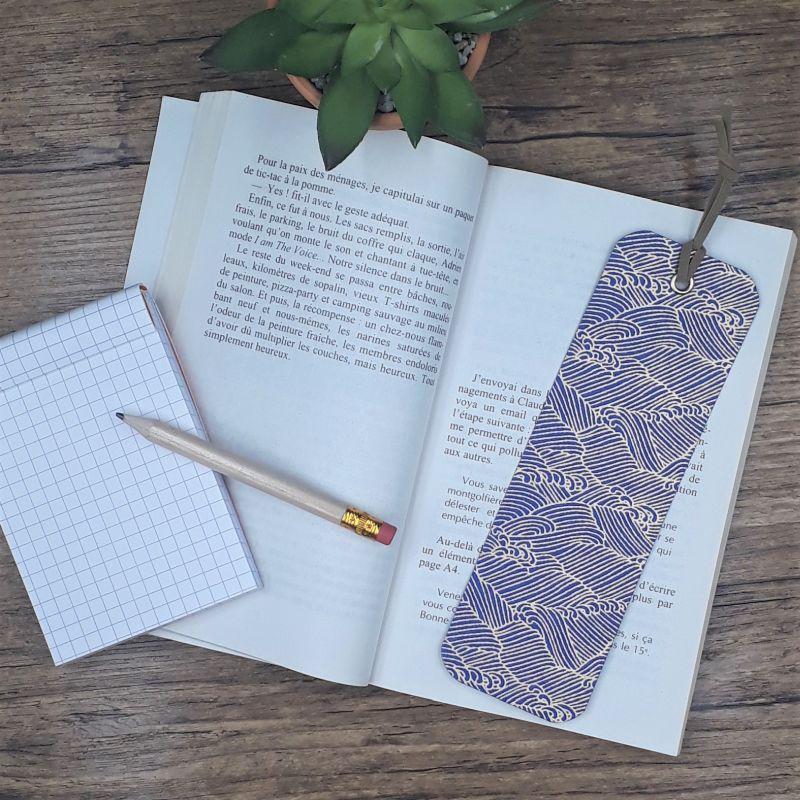 Marque-page artisanal entièrement réalisé à la main dans notre atelier de Lambersart (Lille) recouvert d'un papier japonais bleu roi orné de vagues dorées.