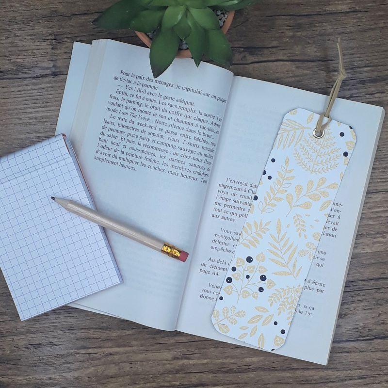 Marque-page artisanal entièrement réalisé à la main dans notre atelier de Lambersart, recouvert de papier japonais écru orné d'un motif de végétaux dorés et de baies noires.