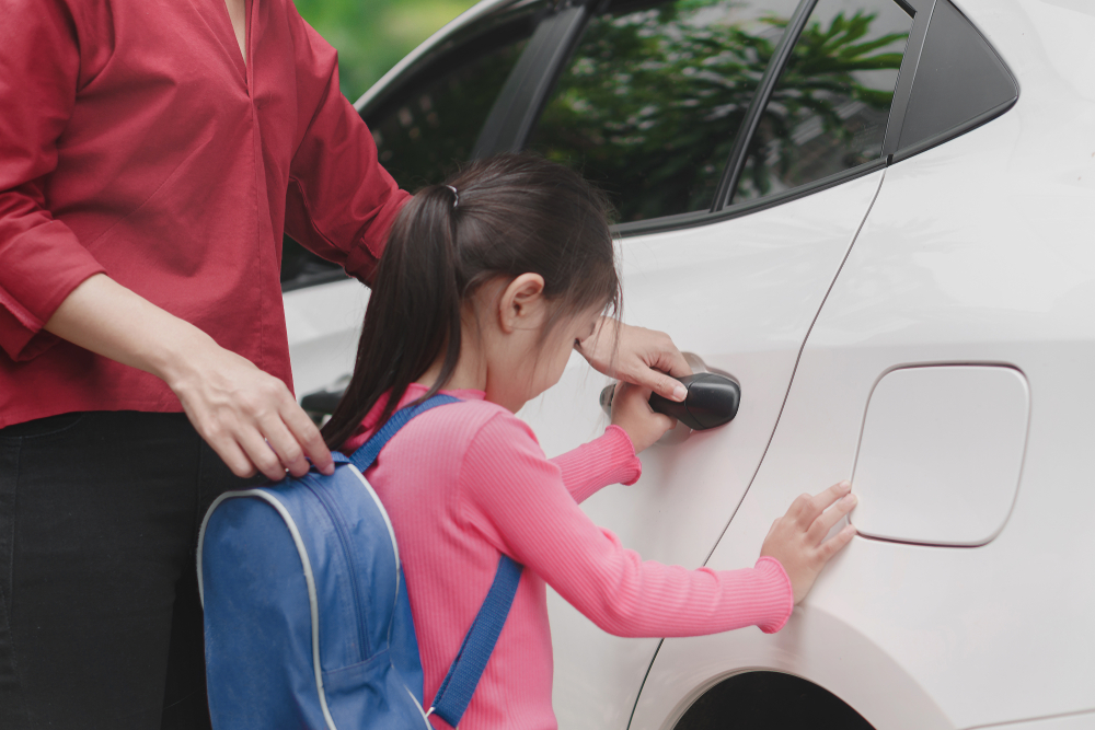 parent helping child into car after being picked up from school