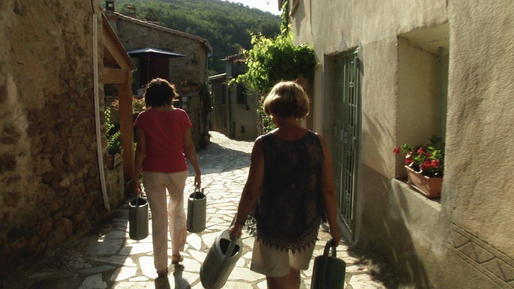 Ruelle de Clara-Villerach à l'heure de l'arrosage. Image du film La vie descend de la montagne, réalisé par Olivier Moulaï pour l'association de Sauvegarde du Canal de Bohère