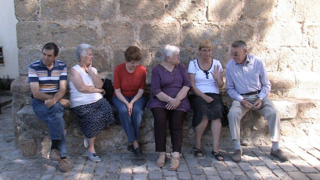 Les habitants de Serralongue discutent sous le clocher du village. Image du film Un phare dans la ville, produit par le festival du carillon de Perpignan, réalisé par Olivier Moulaï.
