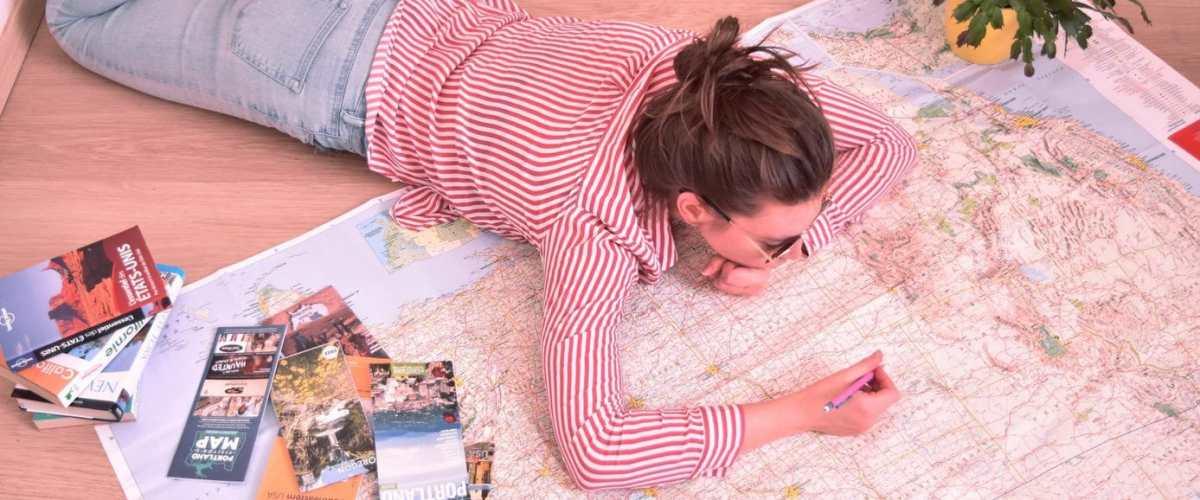 Une fille trace un itinéraire sur une carte routière des Etats-Unis.