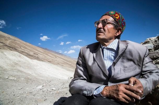 Mahmadwaffa, Wakhi, 63 ans, se repose quelques instants en grimpant la chaine montagneuse du Pamir. Il a revêtu son plus beau costume et son couvre chef traditionnel