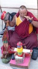 Moine faisant de la musique à l'entrée du Stupa