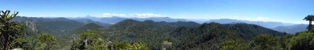 Panorama sur les volcans de la région: à gauche, le pic pointu est le volcan Lanin; sous les nuages, au centre, le volcan Ketrupillan; à droite, le sommet enneigé du volcan Villarica