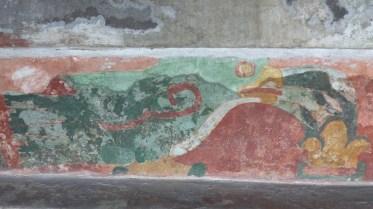 Cette fresque représente un oiseau vert, au bec orange (un quetzal?) devant une fleur