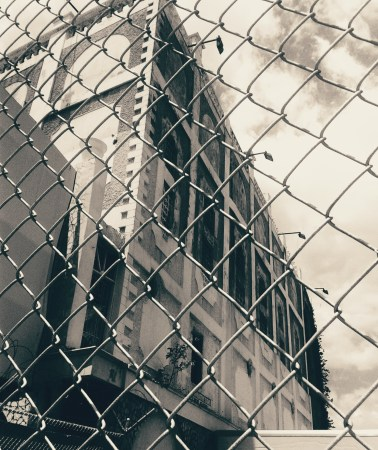 Side view of the abandoned building through the chain-linked fence, in monochrome
