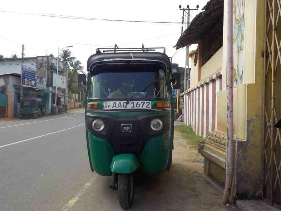 Un tuktuk vert sur le bord de la route à Jaffna
