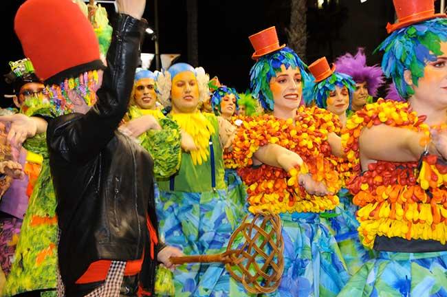 Gente disfrazada de colores vivos, una comparsa de pallasos.