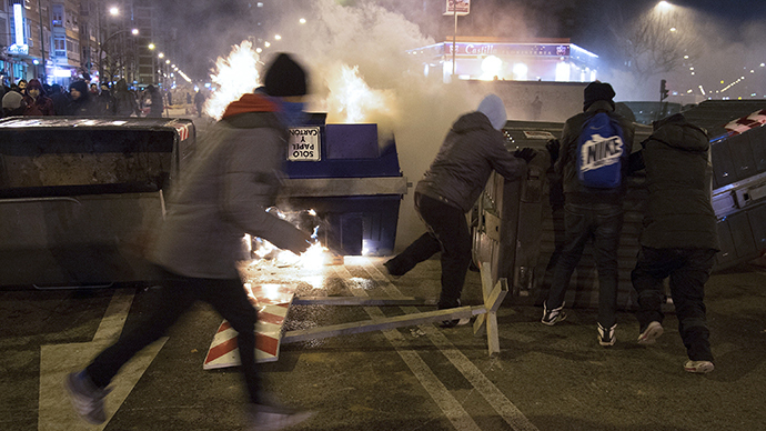 Protesters stand near a burning garbage container during a demonstration against construction plans to turn the Vitoria main avenue into a boulevard in Burgos