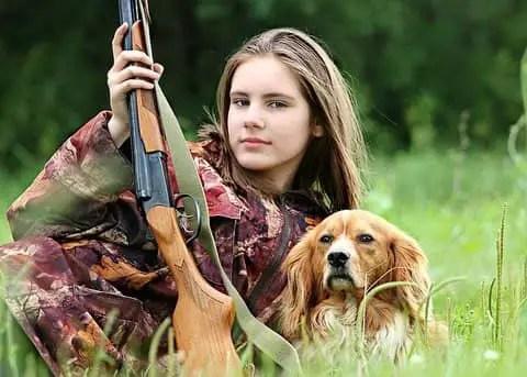 une femme tenant un fusil de chasse avec un chien