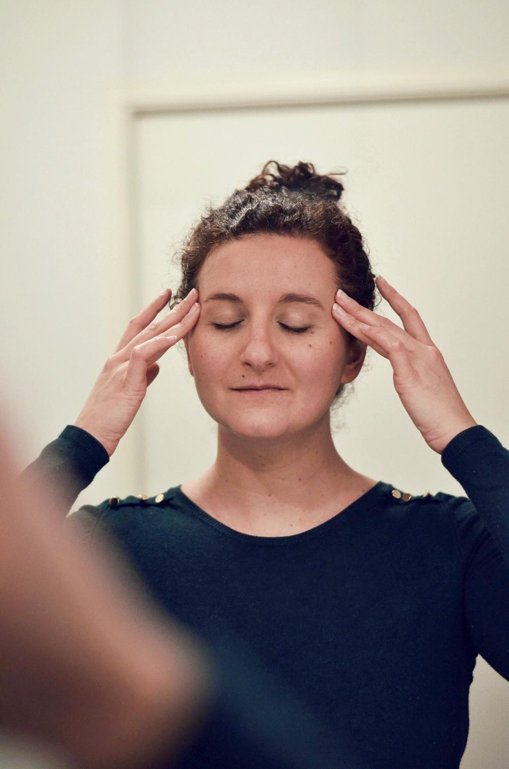 femme se massant le visage devant un miroir