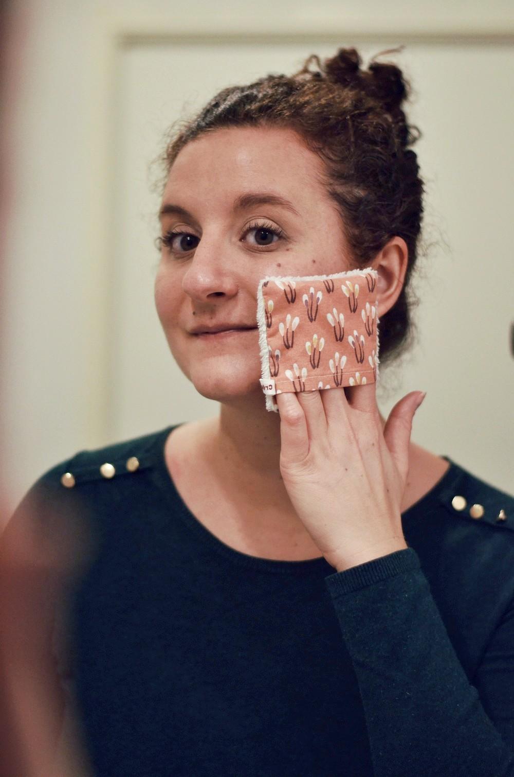 femme se lavant le visage avec un coton lavable devant un miroir