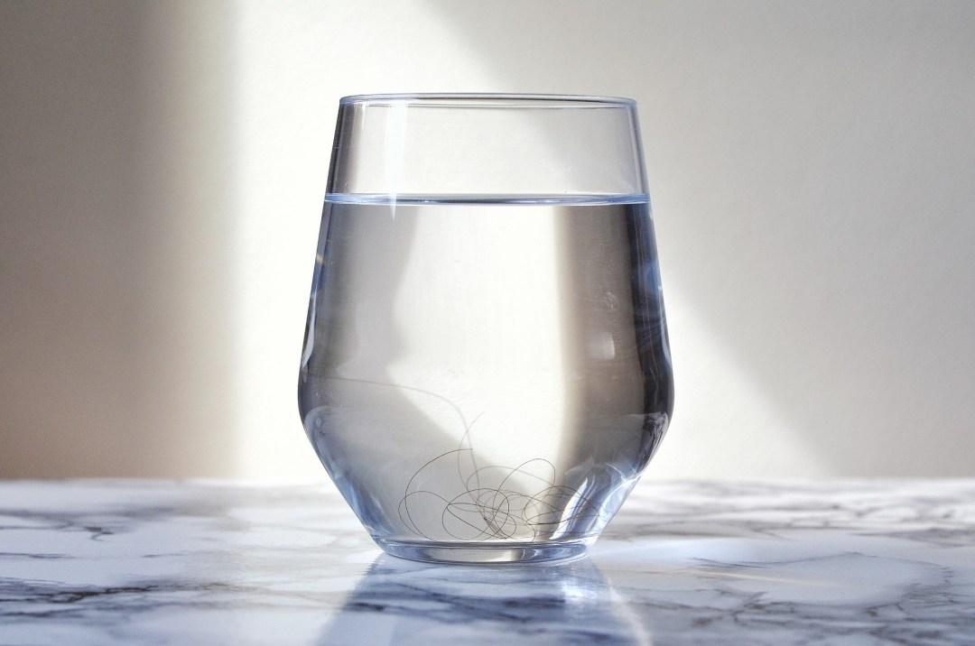 verre d'eau avec cheveux au fond