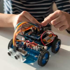 un enfant monte un robot puis le programmera sous Scratch C ou Python