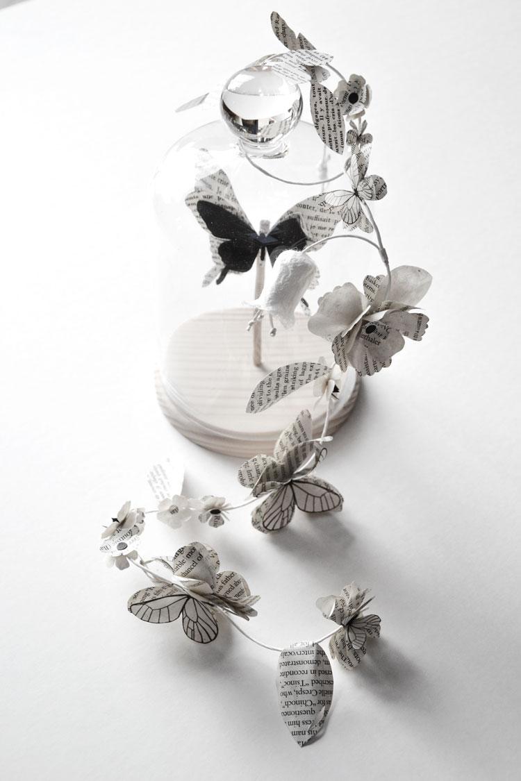 Cloche en verre contenant un papillon noir en papier