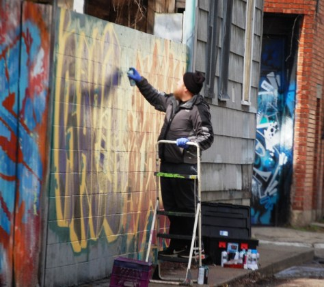 Artist at work on Graffiti wall in Northside