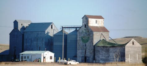 Grain elevators and a barn with a collapsed roof in Bainville, MT on US Route 2