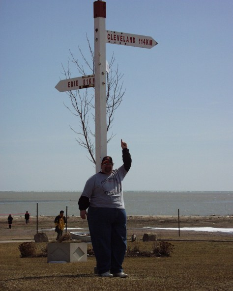 At Lake Erie on the Ontario, Canada side with sign pointing to Cleveland, OH, my birthplace