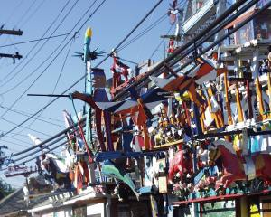 A menagerie of oddball and offbeat things all over the roof, side of the house and the yard - Hamtramck Disneyland