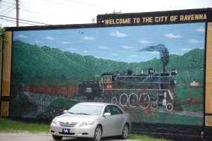 A large mural of a train welcomes visitors to Ravenna, KY