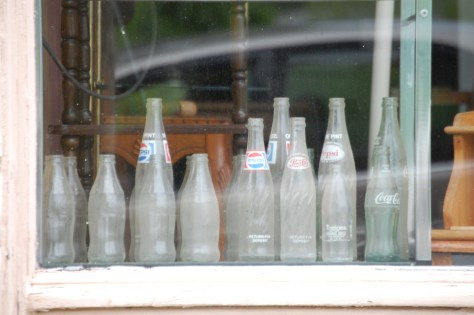 A collection of old soda bottles sits in a window of a store front in Ravenna