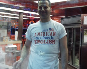 Even the cooks wear shirts about speaking in English at Geno's