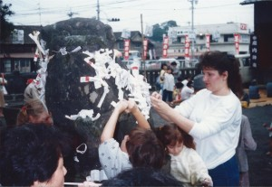 Family putting O-mikuji (prayer papers) on a rock during a celebration in Oita