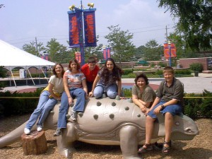 Family climbs aboard a dino at the Indianapolis Children's Museum, Summer 2000