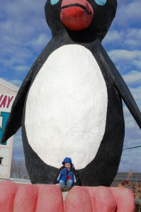 Grandson Charlie is dwarfed by the giant penguin in Cut Bank, Montana