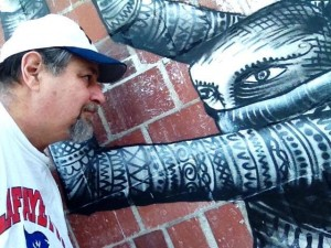 Sumoflam stares down a character from the huge mural just completed by British urban artist Phlegm