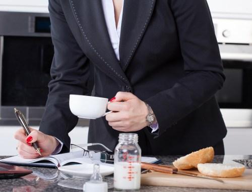 Maman qui reprend le travail après le congé maternité. Table de petit déjeuner sur laquelle on voit un biberon de lait. Femme en veste de tailleur une tasse de café à la main.
