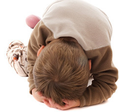 child curled up in a ball to represent caterpillar egg