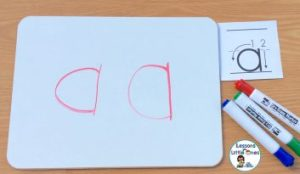 writing alphabet letters on dry erase board