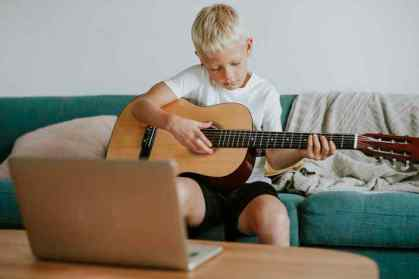 Young boy with acoustic guitar learning to play with online videos.