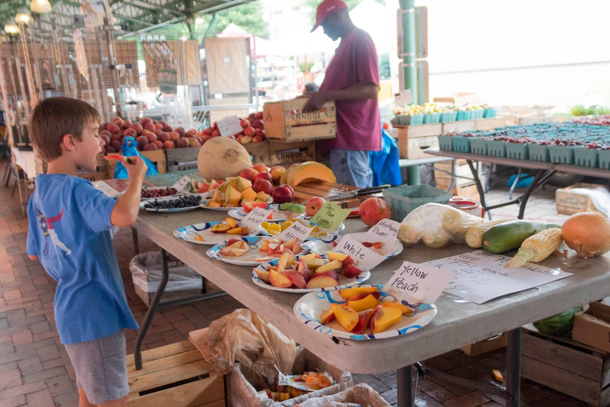 Young boy enjoys fresh fruit in the market