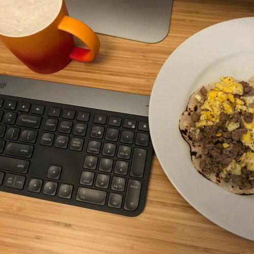 Bamboo desk. Top right has an ombre orange mug with frothy coffee and a silver object which is the base of an iMac computer. Underneath is a black wireless keyboard. To the left, a white plate with charred tortilla with eggs and sausage on top.