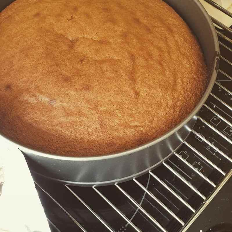 A freshly cooked Victoria sponge in a cake tin.