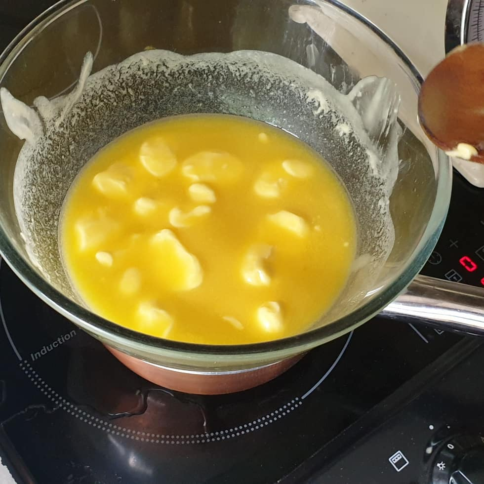 Melting butter in a bowl over a pan of hot water.