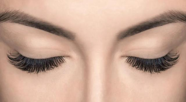 A woman's face focusing on her eyelashes.