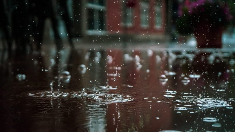 Close up view of rain falling into a puddle