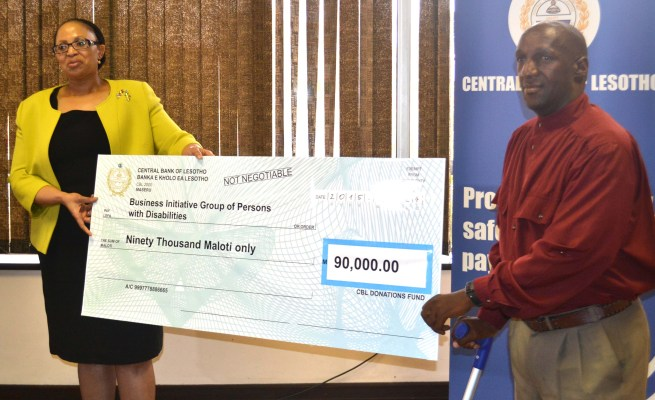 Business Initiative group of Persons with Disability Founder Seabata Lengosane accepts a cheque from governor Matlanyane