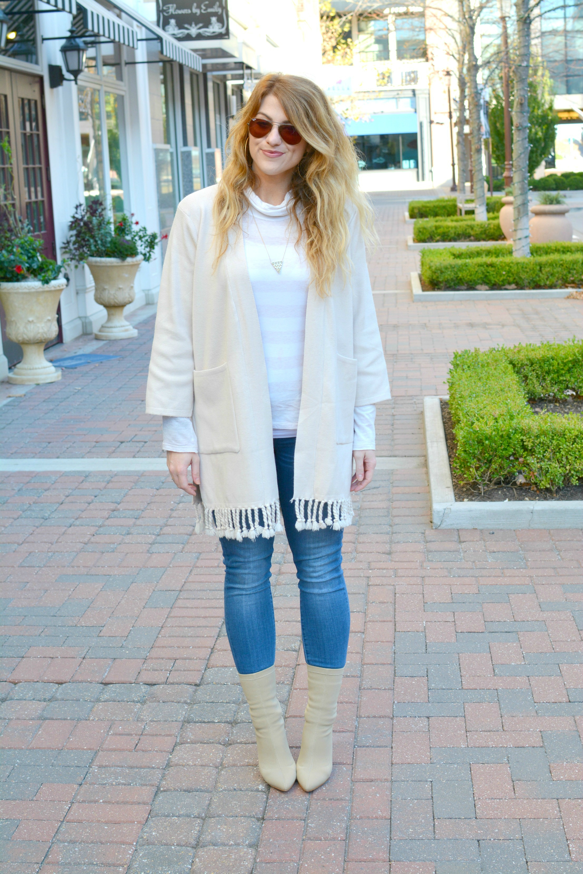 Ashley from LSR in a beige cardigan, skinny jeans, and nude sock boots
