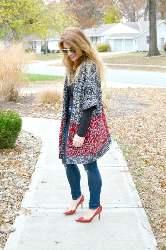 Ashley from LSR in a long cardigan, lace-up bodysuit, and red pumps