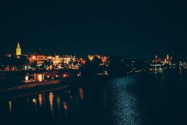 vue de seville la nuit depuis le pont sur la guadalquivir, voyage en espagne