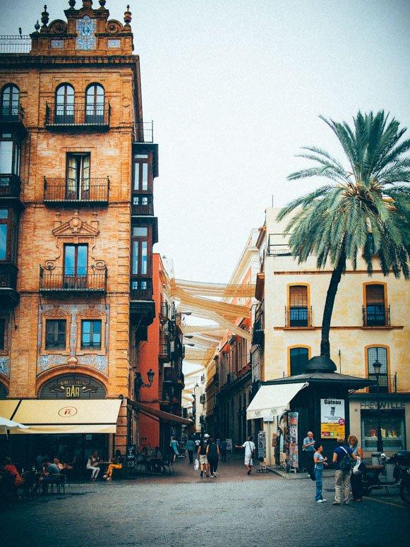 Vue d'une rue avec des voiles depuis une place à seville, voyage en espagne