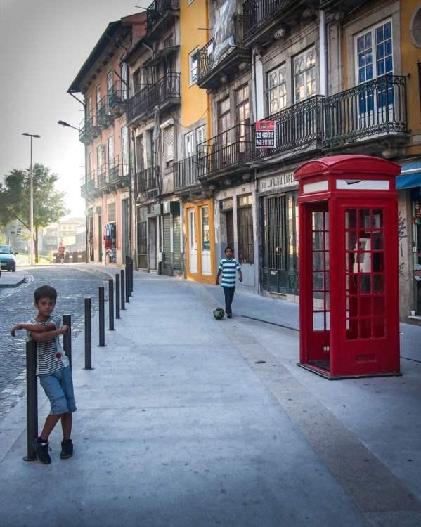 enfants jouent au foot autour d'un cabine téléphonique rouge a porto voyage portugal