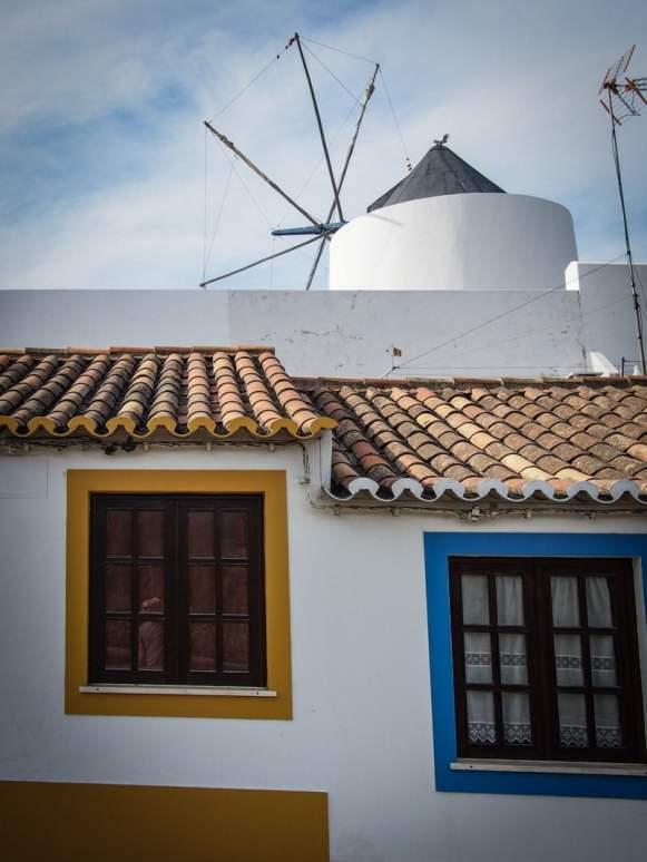 fenêtre jaune et bleu sur fond de moulin a vent a odeceixe au portugal voyage en algarve